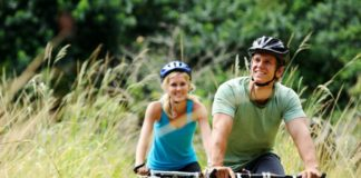 A couple, dressed in mountain biking gear, bike through tall grass. They look very happy.