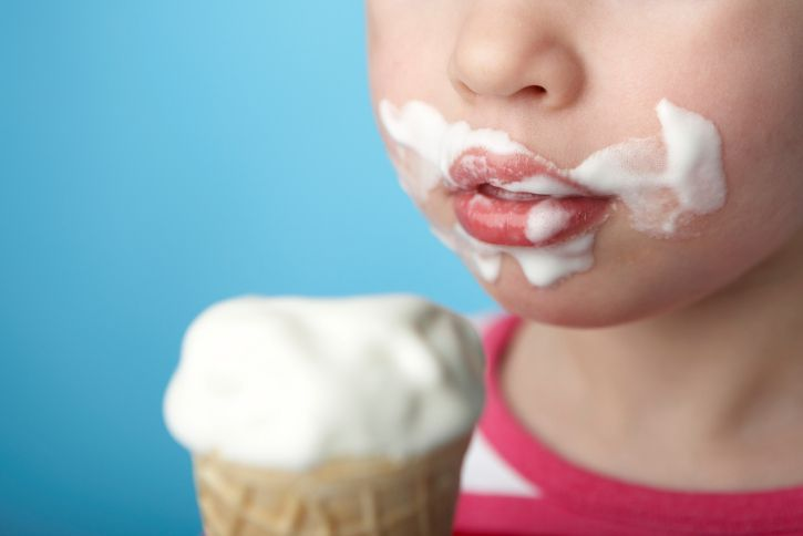 Child with ice cream all over face.