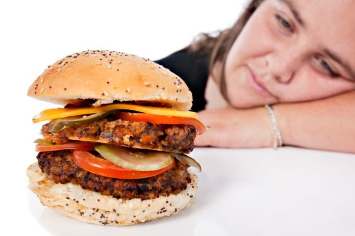 Large burger with woman in the background.