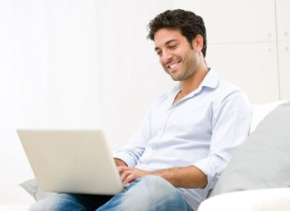A man sits on a couch smiling, using a generic laptop.
