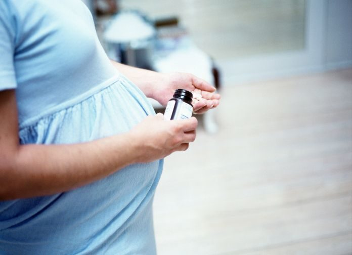 Pregnant woman taking tablets