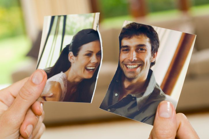 A woman's hands hold a torn photo of a couple
