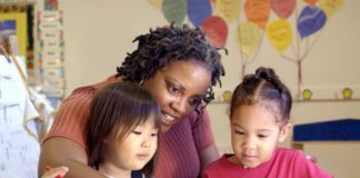 Childcare teacher colors with two little girls.