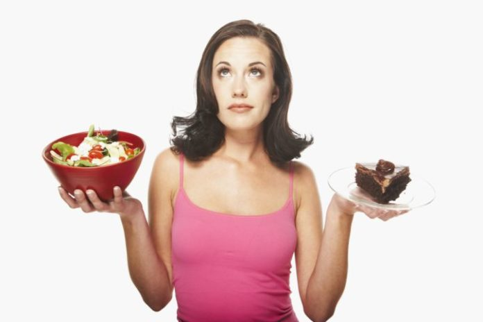 Woman balancing food. In one hand is a salad and in the other, a large piece of chocolate cake.