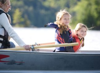 Mother and two daughters in rowboat on the water.