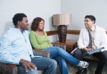 A couple consult with a doctor in what looks to be a waiting room. Everyone is smiling.