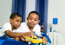 Brothers playing with toy car