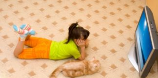 A girls lays on the floor watching TV with her cat.