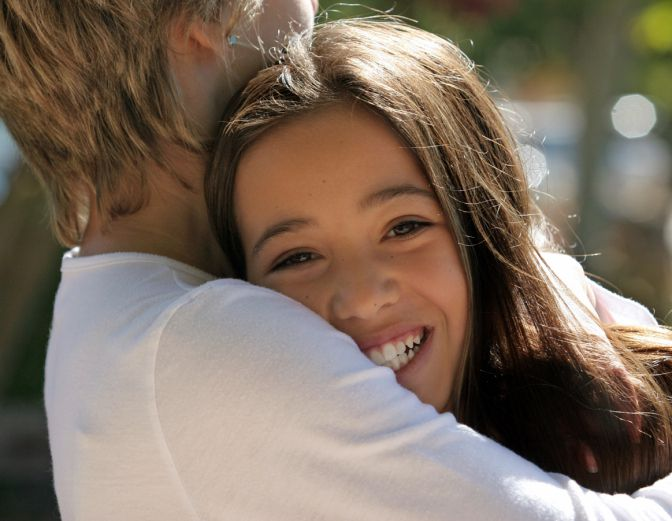 A teenage couple hug. The girl's face is to camera.